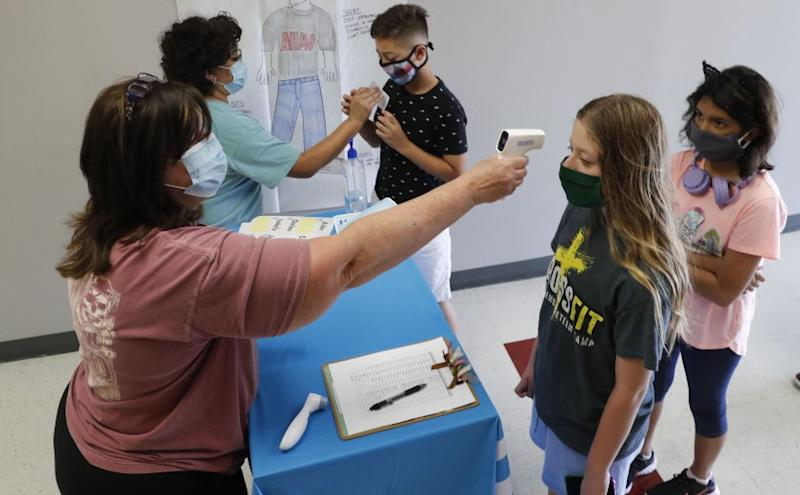 Science teachers Ann Darby, left, and Rosa Herrera check-in students at a school in Wylie, Texas.