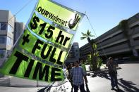 FILE PHOTO: People hold up a sign during a Black Friday protest against Walmart in Long Beach