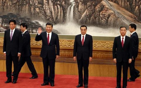 Chinese President Xi Jinping, third from left, waves near Chinese Premier Li Keqiang, third from right, as they walk in with other members of the Chinese Politburo Beijing's at the Great Hall of the People - Credit: AP