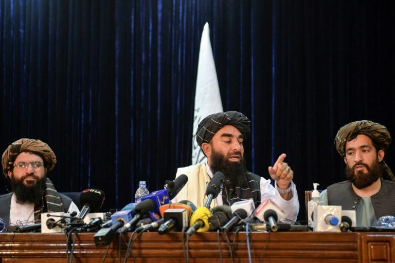 Taliban spokesman Zabihullah Mujahid (center) addresses the first press conference in Kabul following the Taliban's stunning takeover of Afghanistan