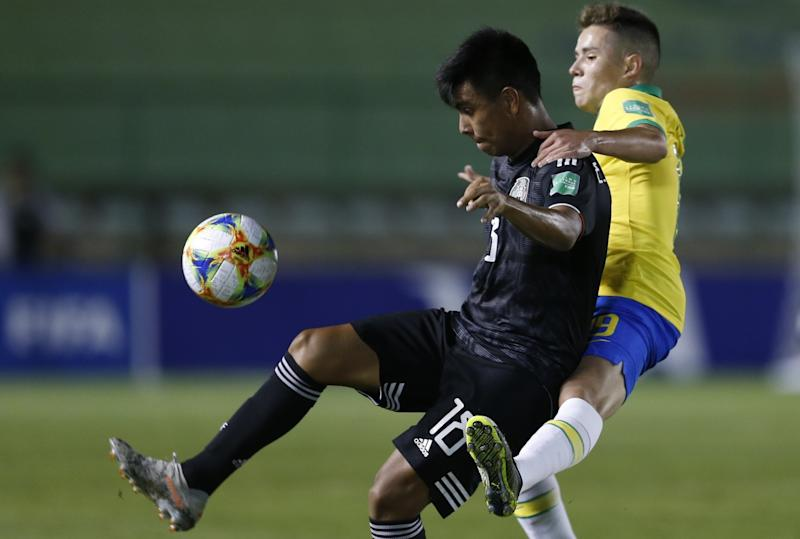 Mexico's Efraín Álvarez, left, fights for the ball with Brazil's Pedro Lucas during the 2019 U-17 World Cup final.
