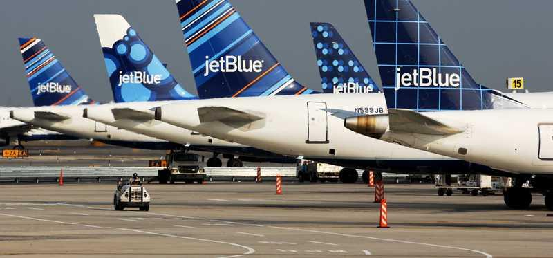 Fleet of JetBlue airplanes at airport gates.