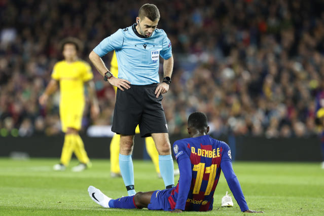 The referee speaks with Barcelona's Ousmane Dembele who had to be substituted after getting injured during a Champions League soccer match Group F between Barcelona and Dortmund at the Camp Nou stadium in Barcelona, Spain, Wednesday, Nov. 27, 2019. (AP Photo/Joan Monfort)