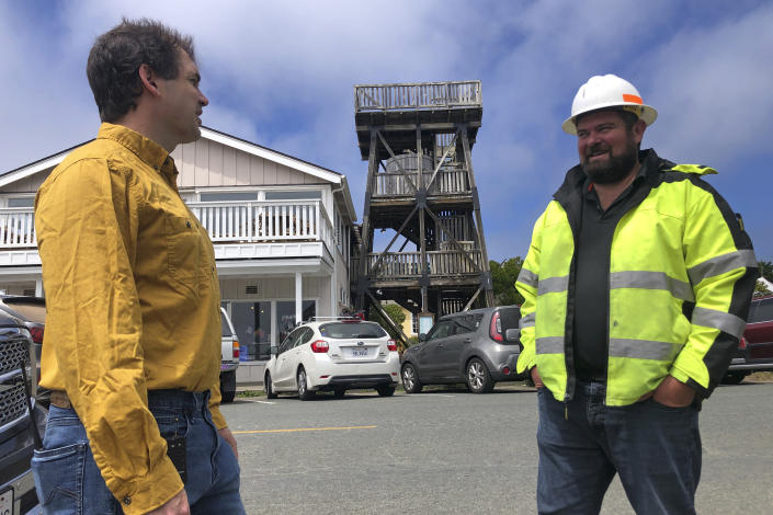 """Mendocino County Supervisor Ted Williams, left, talks with Ryan Rhoades, superintendent of the Mendocino City Community Services District, which helps manage the water in the town's aquifer, in Mendocino, Calif., with an old water tower in the background on Wednesday, Aug. 4, 2021. Tourists flock to the picturesque coastal town of Mendocino for its Victorian homes and cliff trails, but visitors this summer will also find public portable toilets and dozens of signs on picket fences announcing the quaint Northern California hamlet: """"Severe Drought Please conserve water."""" """"This is a real emergency,"""" said Rhoades, """"We need assistance from the state, the county and the federal government."""" (AP Photo/Haven Daley)"""