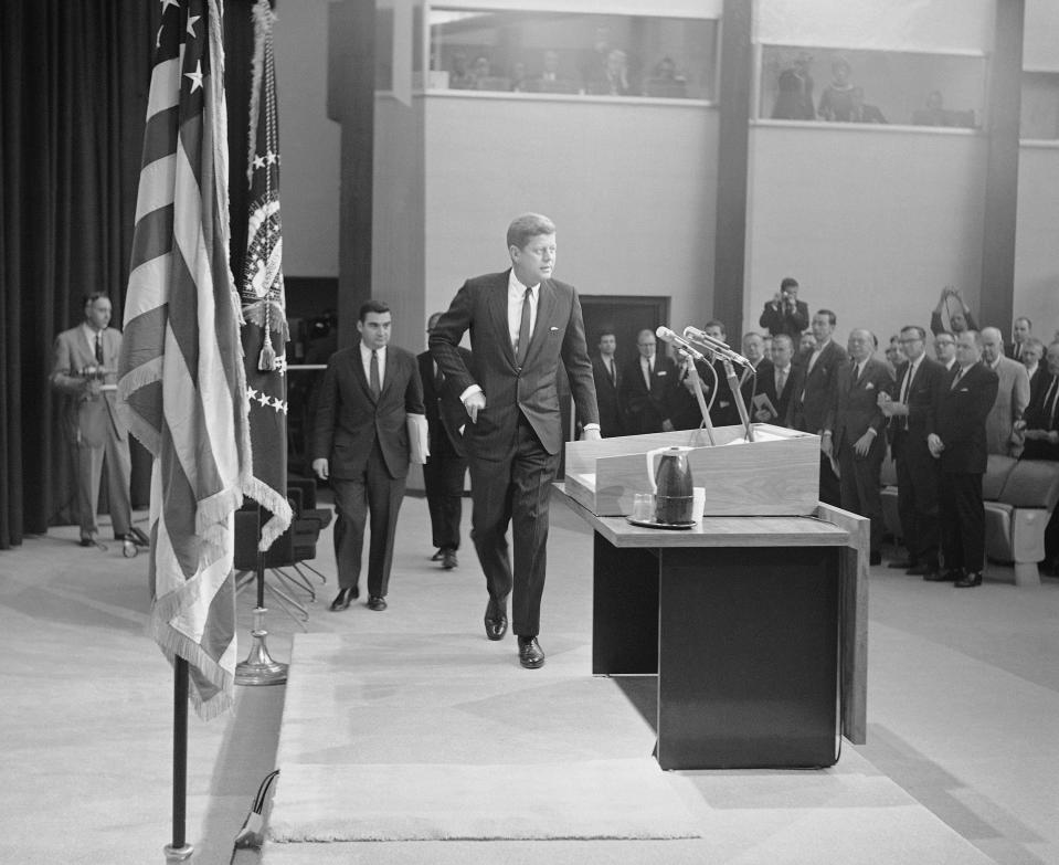 FILE - In this Jan. 25, 1961, file photo President John Kennedy walks toward the rostrum in the auditorium of the new State Department building in Washington to conduct his first news conference as president. Pierre Salinger, White House press secretary, is at left. Reporters stand at right. (AP Photo, File)