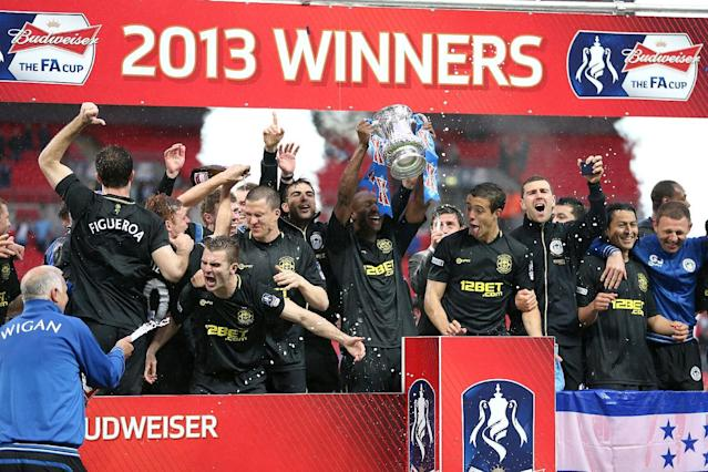 Wigan Athletic players celebrate their victory with the FA Cup trophy, after the final whistle