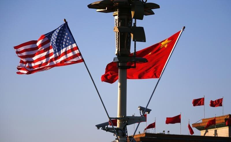 U.S. and Chinese national flags flutter on light post at Tiananmen Square ahead of welcoming ceremony for U.S. President Obama, in Beijing