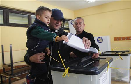 A Kosovo Albanian man places his ballot paper into a voting box at the polling station in the southern part of the divided town of Mitrovica in Kosovo, November 3, 2013. REUTERS/Hazir Reka