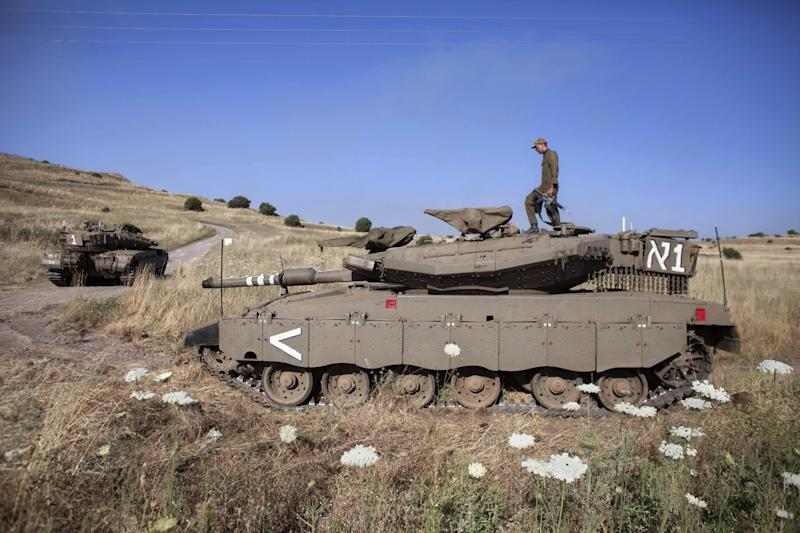An Israeli soldier walks atop a tank near the Quneitra crossing to Syria, Thursday, June 6, 2013. Syrian rebels on Thursday captured a crossing point along a cease-fire line with Israel in the contested Golan Heights, a development that could deepen Israeli concerns over the growing role of Islamic radicals in the civil war near its northern frontier.(AP Photo/Sebastian Scheiner)