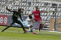 Austin FC midfielder Cecilio Dominguez, center, heads the ball against Los Angeles FC goalkeeper Pablo Sisniega, right, while Jesus David Murillo, left, defends during the first half of an MLS soccer match Saturday, April 17, 2021, in Los Angeles. (AP Photo/Ringo H.W. Chiu)