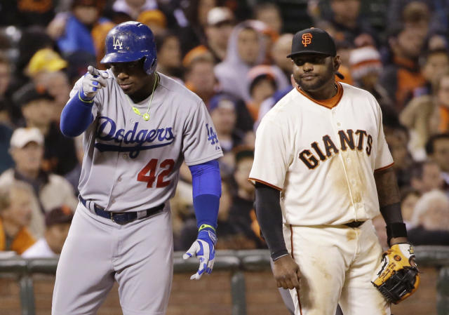 Los Angeles Dodgers' Yasiel Puig, left, points to his dugout after a triple next to San Francisco Giants third baseman Pablo Sandoval during the eighth inning of a baseball game on Tuesday, April 15, 2014, in San Francisco. (AP Photo/Marcio Jose Sanchez)