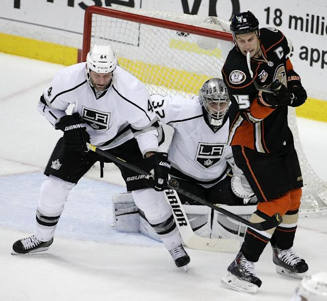 Anaheim Ducks center Ryan Getzlaf, right, battles Los Angeles Kings defenseman Robyn Regehr, left, for the puck as goalie Jonathan Quick looks on during the first period of an NHL hockey game in Anaheim, Calif., Thursday, Jan. 23, 2014. (AP Photo/Chris Carlson)