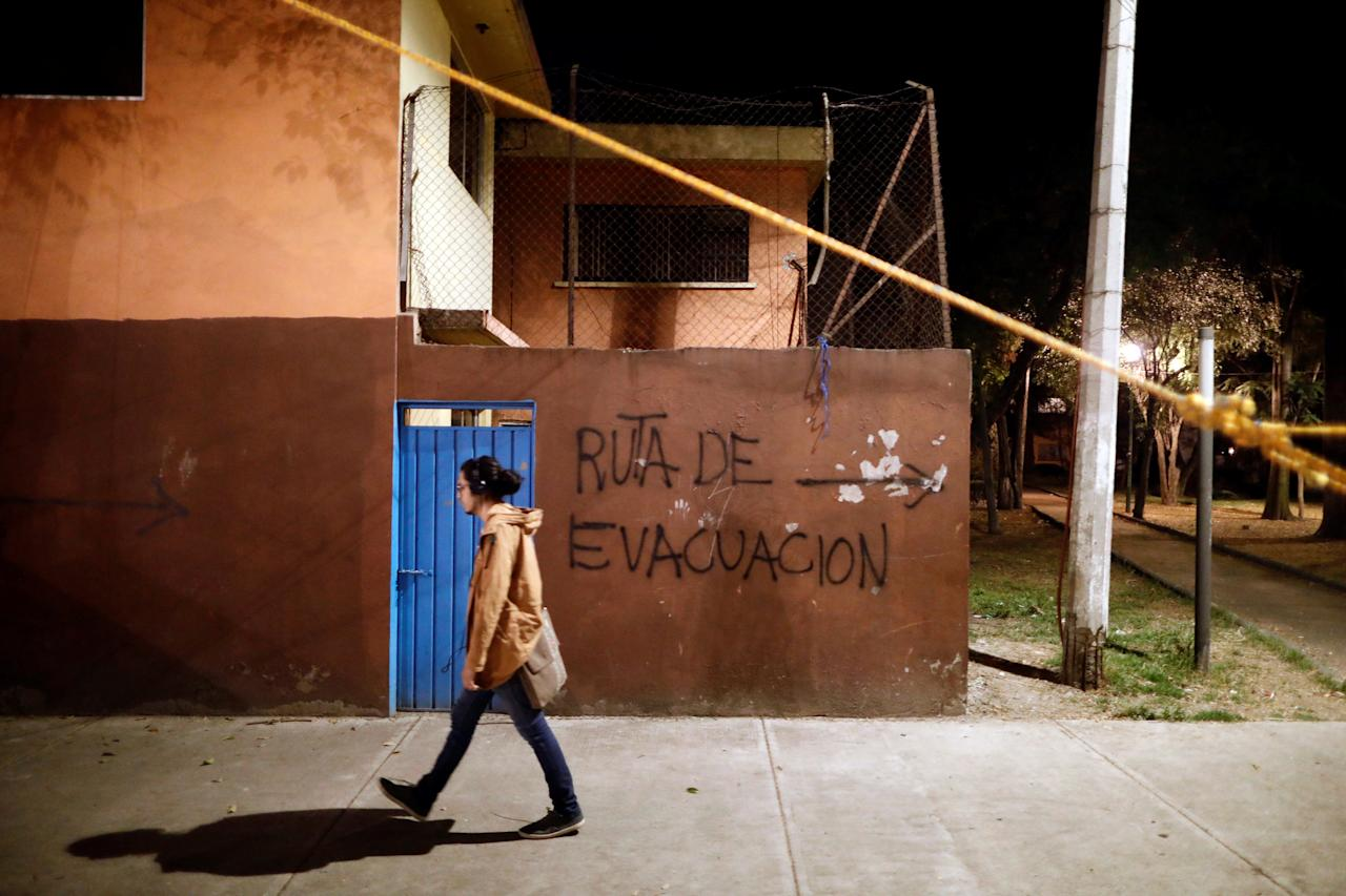 "A man walks past a graffiti reading ""Evacuation route"" at a makeshift shelter for families affected by the earthquake that hit the Tlalpan housing project, five months after the September 19 earthquake, in the Educacion neighborhood in Mexico City, Mexico February 16, 2018. Picture taken February 16, 2018. REUTERS/Edgard Garrido"
