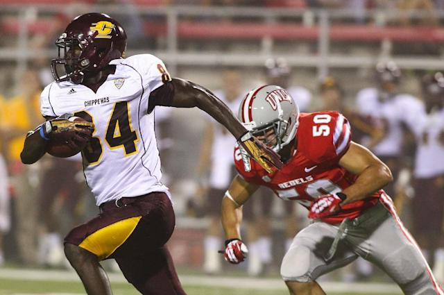 Central Michigan's Titus Davis (84) runs past UNLV's Trent Langham (50) during the first half of an NCAA college football game at Sam Boyd Stadium in Las Vegas on Saturday, Sept. 14, 2013. (AP Photo/Las Vegas Review-Journal, Chase Stevens)