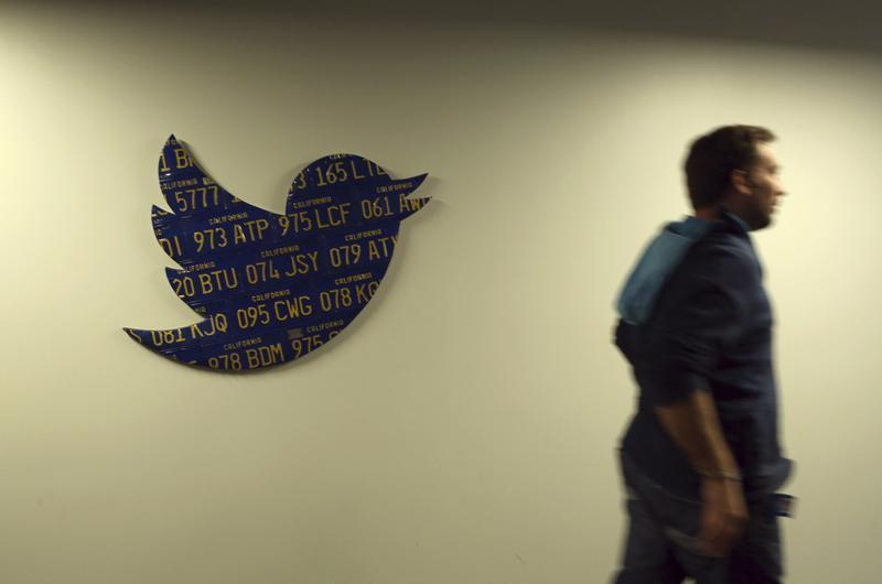 An employee walks past a Twitter logo made from Californian license plates at the company's headquarters in San Francisco