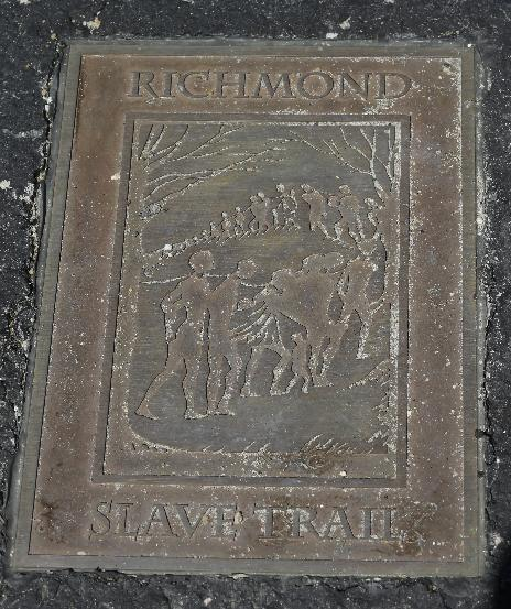 A historical marker is embedded in the walkway near the Lumpkin Jail historical site at the Slave Burial GroundMonday, March 31, 2014. A proposal to build a minor league baseball stadium in Shockoe Bottom, the city's oldest neighborhood and the center of the once-thriving slave trade, has drawn criticism from some who believe the area is sacred ground and shouldn't be bulldozed for a ballpark. The city says it will recover and display artifacts related to the slave trade.(AP Photo/Steve Helber)