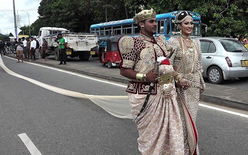 TheSri Lankan wedding couple walk along a road as as a bride attempts to set a record for the longest wedding saree - AFP