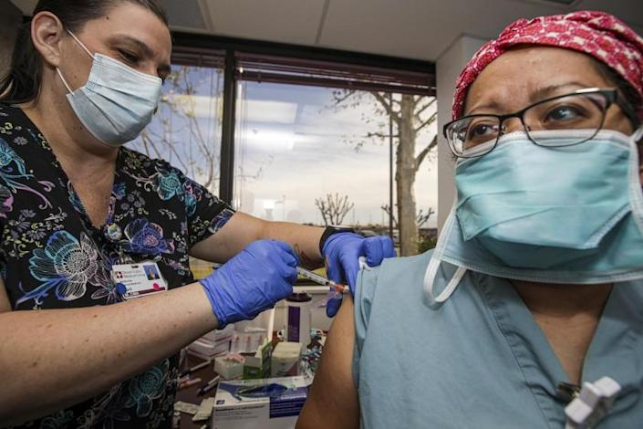 Victorville, CA - December 17: Medical assistant April Massaro, left, gives first dose of Pfizer BioNTech COVID-19 vaccine to nurse Alice Fallago at Desert Valley Hospital on Thursday, Dec. 17, 2020 in Victorville, CA. (Irfan Khan / Los Angeles Times)