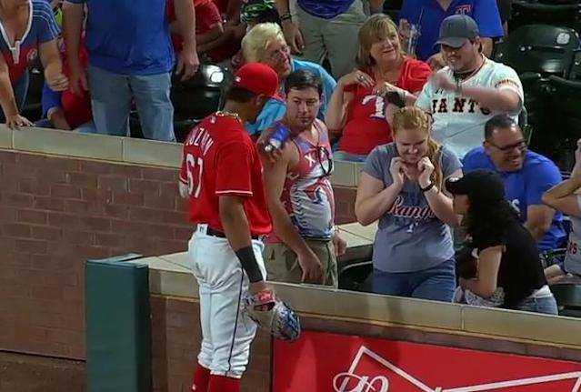 Texas Rangers rookie Ronald Guzman jokingly borrows a fan's phone during Friday's game against the Kansas City Royals. (MLB.TV)