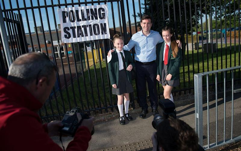 Andy Burnham poses with his daughters Annie and Rosie as he arrives at Golborne Community Primary school to cast his vote in the Greater Manchester mayoral election, for which he is standing as a candidate - Credit: Oli Scarff/AFP