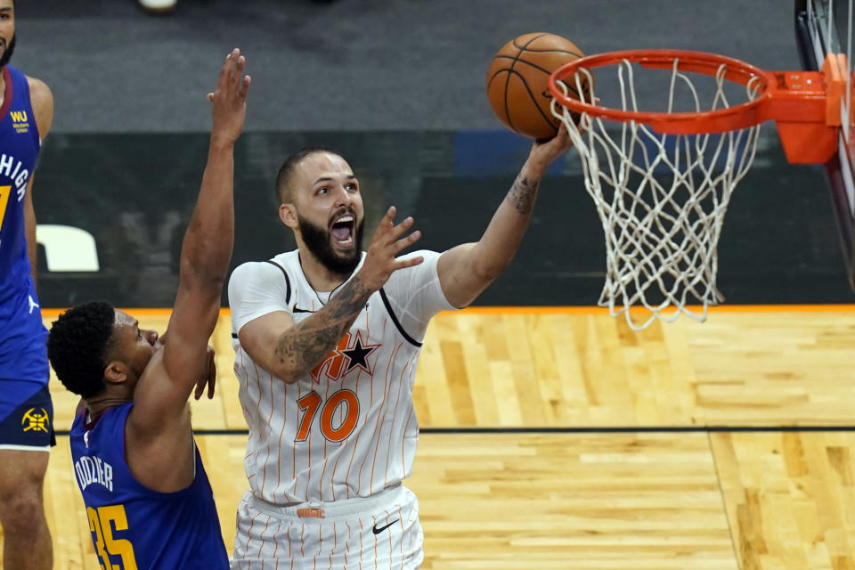 Orlando Magic guard Evan Fournier (10) gets past Denver Nuggets guard PJ Dozier, left, for a shot during the second half of an NBA basketball game, Tuesday, March 23, 2021, in Orlando, Fla. (AP Photo/John Raoux)