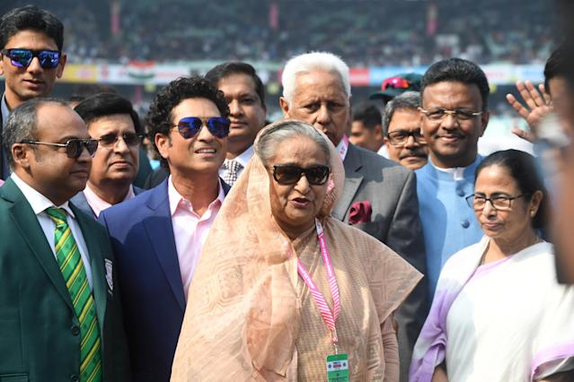 Bangladesh's Prime Minister Sheikh Hasina (C) speaks as West Bengal Chief Minister Mamata Banerjee (R) and former Indian cricketer Sachin Tendulkar (4th L) watch before the start of the first day of the second Test cricket match of a two-match series between India and Bangladesh at The Eden Gardens cricket stadium in Kolkata on November 22, 2019. (Photo by Dibyangshu SARKAR / AFP) / IMAGE RESTRICTED TO EDITORIAL USE - STRICTLY NO COMMERCIAL USE