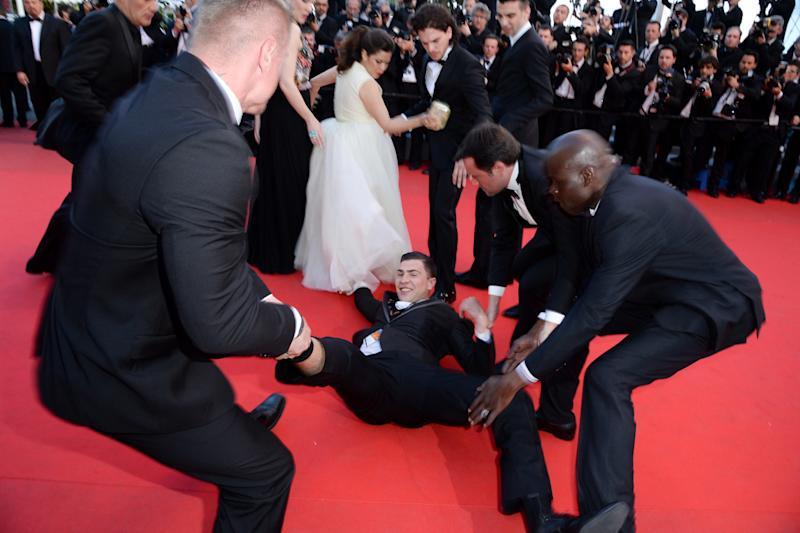 Sediuk being pulled away by security guards after climing under Ferrera's dress. (Photo: Getty Images)