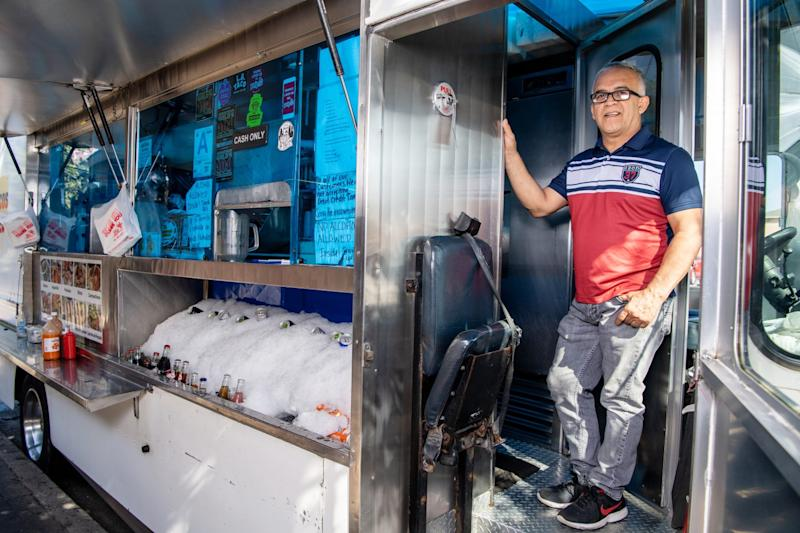 Mariscos Jaliscos owner Raul Ortega stands in the doorway of his food truck.