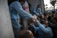 Palestinian workers unload a truck from 20,000 doses of Russian-made Sputnik V vaccine upon its arrival to Gaza Strip, at the Rafah crossing border with Egypt, Sunday, Feb. 21, 2021. The 20,000 doses of Russia's Sputnik V, donated by the United Arab Emirates and organized by Abbas rival Mohammed Dahlan, entered the Palestinian enclave through its border with Egypt. (AP Photo/Khalil Hamra)