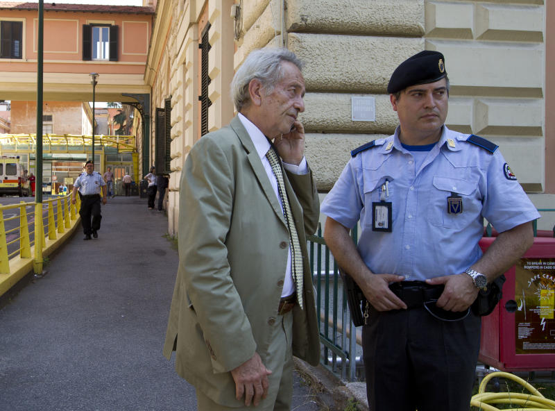 Director Claudio Modini, head of the emergency room at the Policlinico Umberto I hospital, left, speaks on a mobile phone outside the emergency room entrance of the hosptal, in Rome,Thursday June 20, 2013. Hospital officials said actor James Gandolfini, 51, died after suffering a cardiac arrest on Wednesday while vacationing in Rome. Modini, said Gandolfini arrived at the hospital at 10:40 p.m. (2040 GMT, 4:40 p.m. EDT) Wednesday and was pronounced dead at 11 p.m. after resuscitation efforts in the ambulance and hospital failed. (AP Photo/Alessandra Tarantino)
