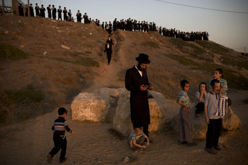 Ultra-Orthodox Jews of the Hassidic sect Vizhnitz gather on a hill overlooking the Mediterranean sea as they participate in a Tashlich ceremony in Herzeliya, Israel, Thursday, Sept. 12, 2013. Tashlich, which means 'to cast away' in Hebrew, is the practice by which Jews go to a large flowing body of water and symbolically 'throw away' their sins by throwing a piece of bread, or similar food, into the water before the Jewish holiday of Yom Kippur, which start on Friday. (AP Photo/Oded Balilty)