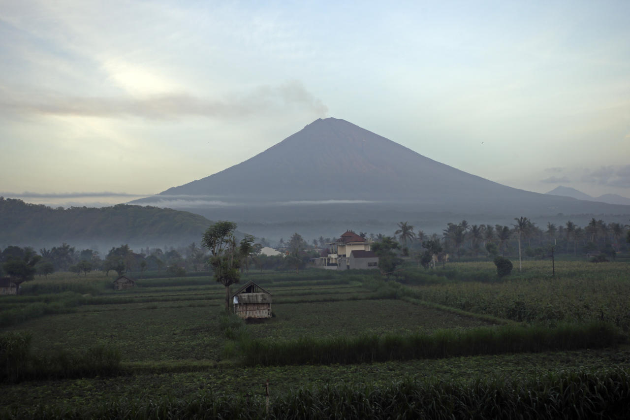 Mount Agung volcano spews smoke in Karangasem, Bali, Indonesia, Monday, Dec. 4, 2017. Gushing ash from Bali's Mount Agung volcano has dissipated into a wispy plume of steam. Indonesia's disaster mitigation agency said Monday the volcano remains at its highest alert level but most of Bali is safe for tourists. (AP Photo/Firdia Lisnawati)