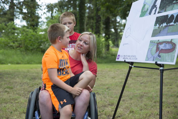 Missy Jenkins Smith, who was shot during the Heath High School shooting in 1997 and paralyzed from the chest down, talks to her sons, Carter Smith, 7, and Logan Smith, 9, about the shooting. (Photo: Ryan Hermens/The Paducah Sun via AP)