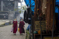 Exile Tibetan Buddhist monks wearing masks as a precautionary measure against the coronavirus walks in a deserted market area in Dharmsala, India, Friday, Sept. 11, 2020. India's coronavirus cases are now the second-highest in the world and only behind the United States. (AP Photo/Ashwini Bhatia)