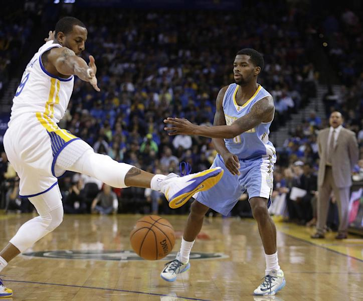 Denver Nuggets' Aaron Brooks, right, passes below the leg of Golden State Warriors' Andre Iguodala during the first half of an NBA basketball game Thursday, April 10, 2014, in Oakland, Calif. (AP Photo/Ben Margot)