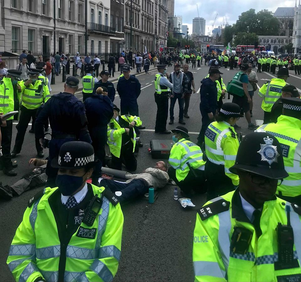 Police attempt to move XR protesters who've glued themselves to the ground (Holly Bancroft/The Independent)
