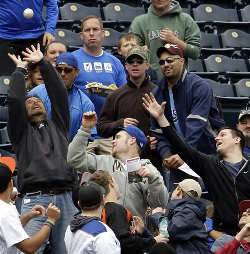 Fans battle for a foul ball hit by Kansas City Royals' Alex Gordon during the third inning of a baseball game against the Toronto Blue Jays, Sunday, April 22, 2012, in Kansas City, Mo. (AP Photo/Charlie Riedel)