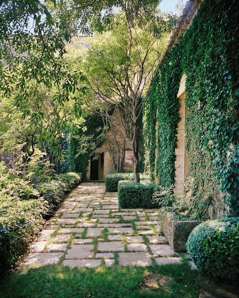 """Boxwood spheres and cubes—""""I think I have more boxwood than anybody in the world,"""" Tarlow says—bring green geometry to a stone terrace."""