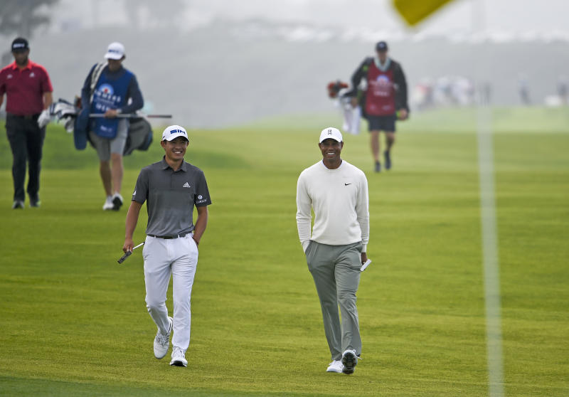 Collin Morikawa, left foreground, talks with Tiger Woods as they walk on the fourth hole of the South Course at Torrey Pines Golf Course during the second round of the Farmers Insurance golf tournament Friday Jan. 24, 2020, in San Diego. (AP Photo/Denis Poroy)