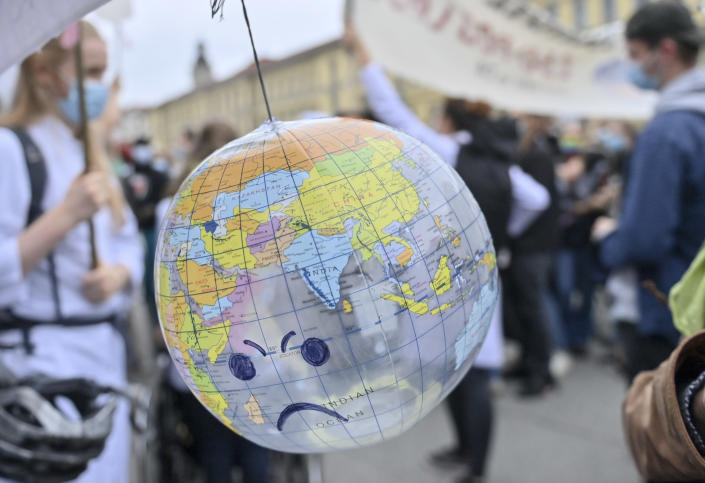 People hold banners and gather to rally against global warming and climate change in Leipzig, Germany, Friday Sept. 24, 2021. (Hendrik Schmidt/dpa via AP) :