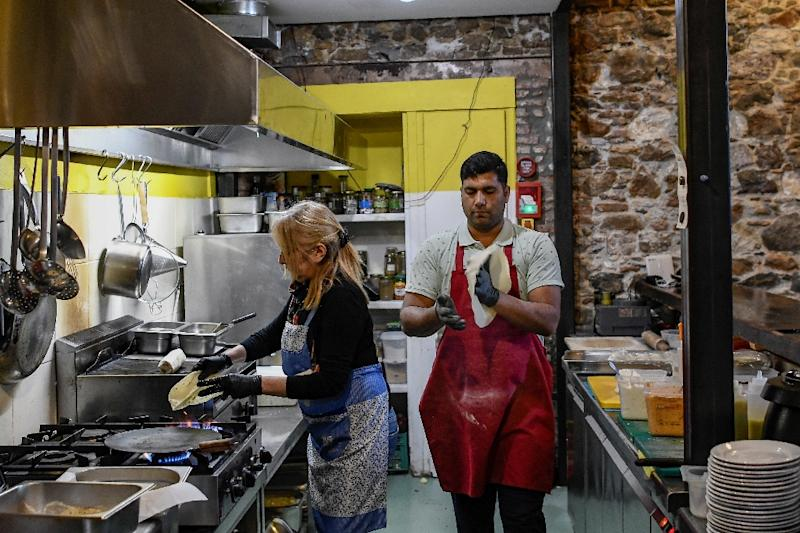 Abdul from Pakistan has found work at a restaurant on the island, but many other newcomers struggle (AFP Photo/ARIS MESSINIS)