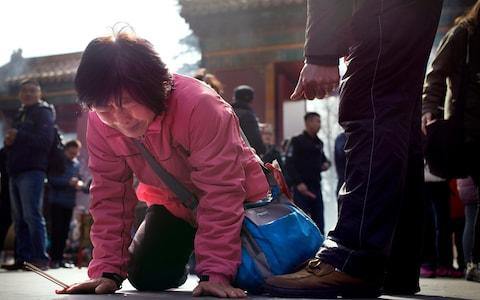 <span>A woman cries and drops to her knees while praying with MH370 relatives at the Lama Temple in Beijing, on the second anniversary of plane's disappearance</span> <span>Credit: &nbsp;Mark Schiefelbein </span>