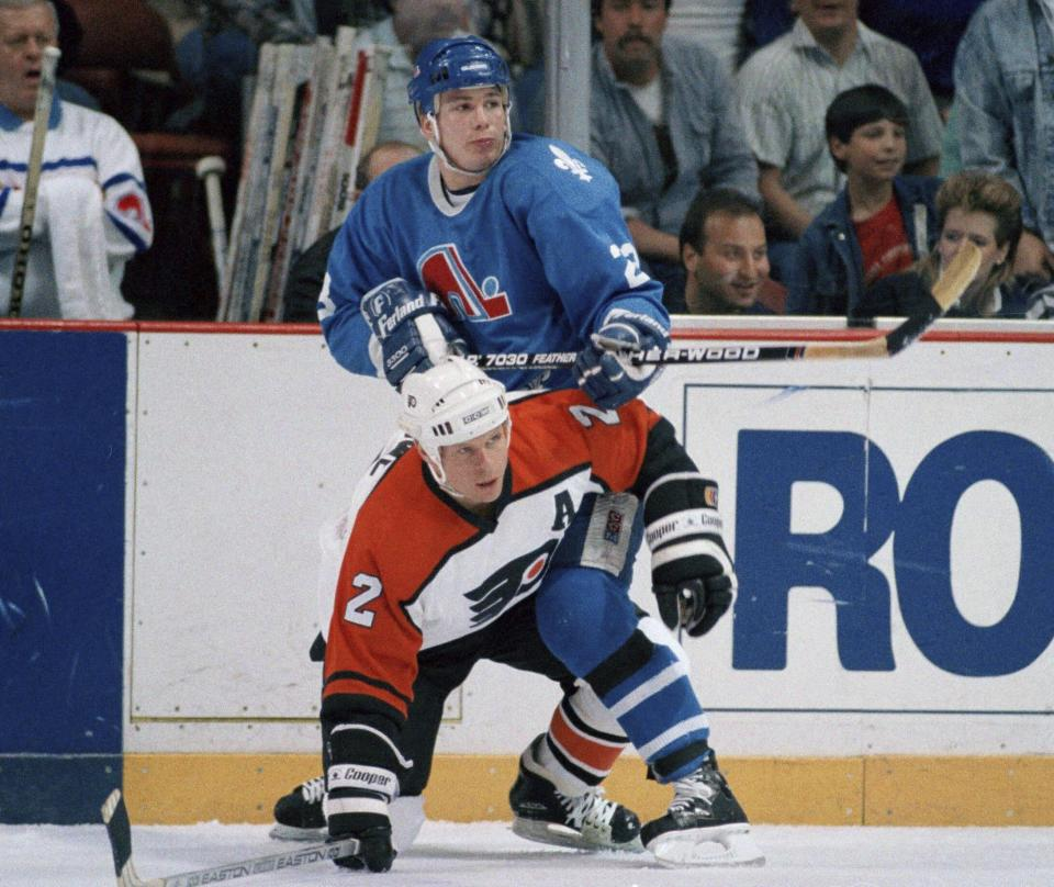 FILE - In this March 31, 1988, file photo, Quebec Nordiques' Paul Gillis holds Philadelphia Flyers' Mark Howe (2) to the ice with his knee during first-period NHL hockey game action in Philadelphia. New York Rangers' Brendan Smith and Florida Panthers Mark Pysyk are the latest to follow the lead of Hall of Famers Red Kelly and Howe and present-day Brent Burns and Dustin Byfuglien, and their experience could open the door for more multiposition players in a sport that usually defines being a center, winger or defenseman very specifically. (AP Photo/Amy Sancetta, File)