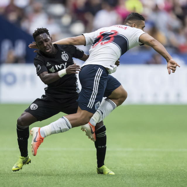 Vancouver Whitecaps' Ali Adnan, front right, is upended by Sporting Kansas City's Gerso Fernandes during the first half of an MLS soccer match Saturday, July 13, 2019, in Vancouver, British Columbia. (Darryl Dyck/The Canadian Press via AP)