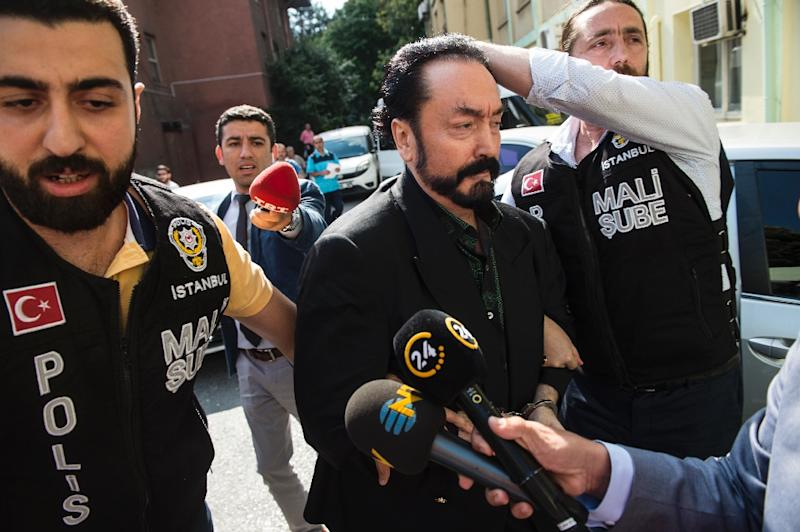 Turkish police officers escort televangelist Adnan Oktar (centre) following his arrest in Istanbul, on July 11, 2018