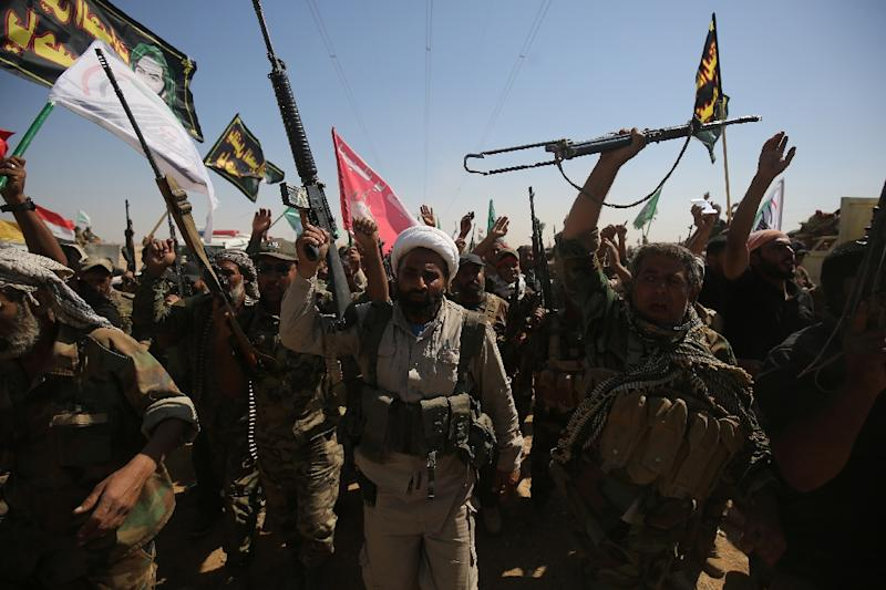 Iraqi fighters from the Hashed al-Shaabi paramilitary organisation mark Ashura, commemorating the killing of Imam Hussein, one of Shiite Islam's most revered figures, as they advance on Islamic State group positions on October 1, 2017 (AFP Photo/AHMAD AL-RUBAYE)