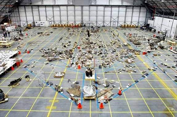 An overview of the Columbia debris reconstruction hangar in 2003 shows the orbiter outline on the floor with some of the 78,760 pieces identified to that date. More than 84,000 pieces of shuttle debris were recovered, some of which is included