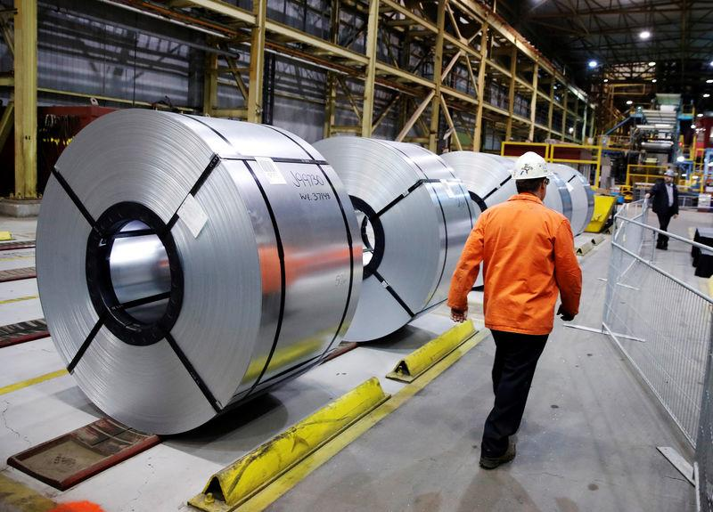 FILE PHOTO: A worker walks by rolled up steel sits in the ArcelorMittal Dofasco steel plant in Hamilton, Ontario