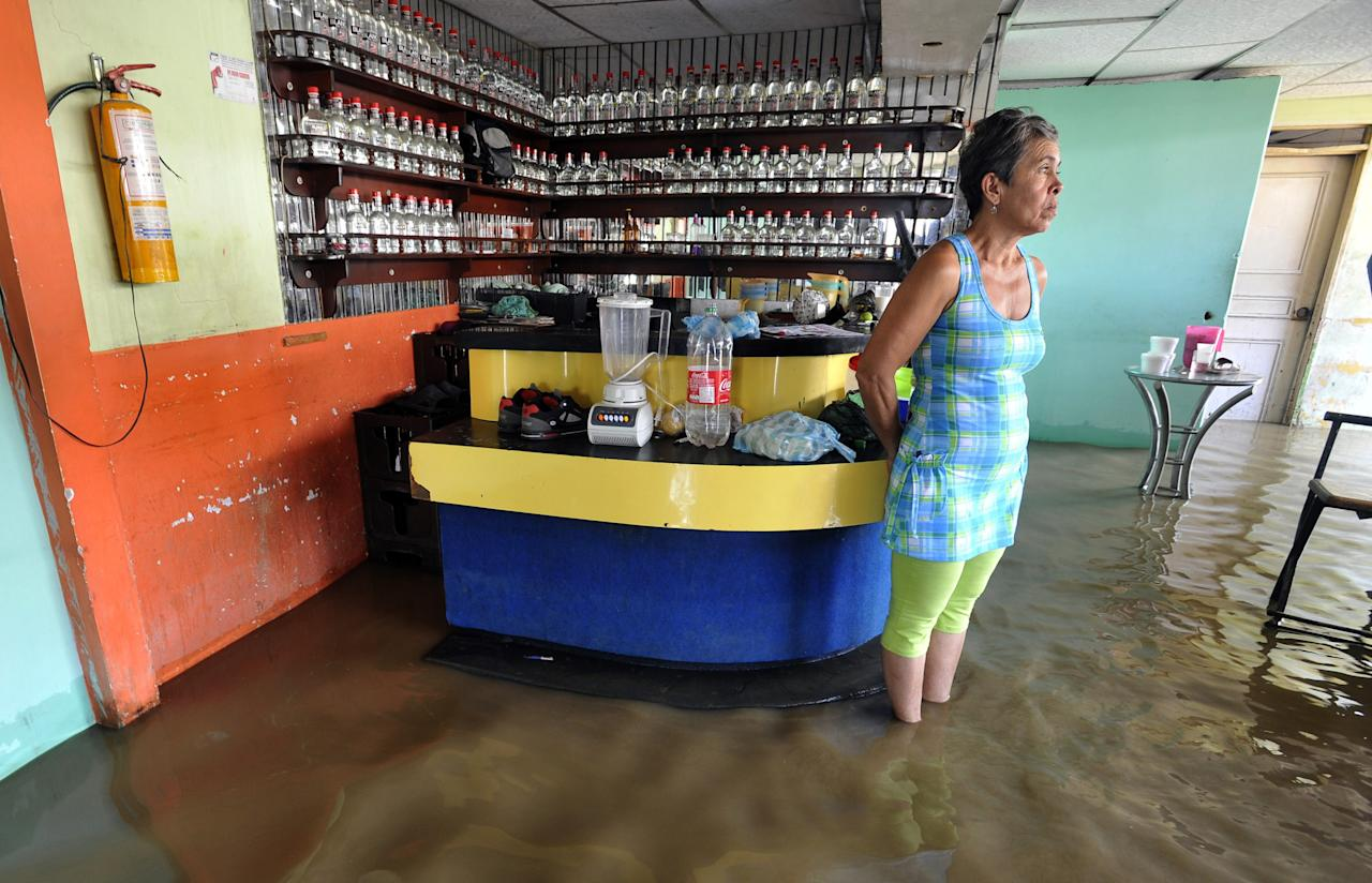FILE - In this Dec. 7, 2011 file photo, a woman stands in a flooded disco in Juanchito, Colombia. From Chile to Colombia to Mexico, Latin America has been battered recently by wildfires, floods and droughts. While leading climate scientists are unable to pin any single flood or heat wave solely on climate change, experts say the number of extreme weather events is increasing worldwide and the evidence suggests global warming is having an impact. (AP Photo/Carlos Julio Martinez, File)
