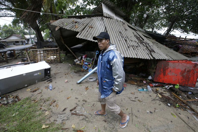 A man inspects his house damaged by a tsunami in Carita, Indonesia, Sunday, Dec. 23, 2018. The tsunami occurred after the eruption of a volcano around Indonesia's Sunda Strait during a busy holiday weekend, sending water crashing ashore and sweeping away hotels, hundreds of houses and people attending a beach concert. (AP Photo/Achmad Ibrahim)